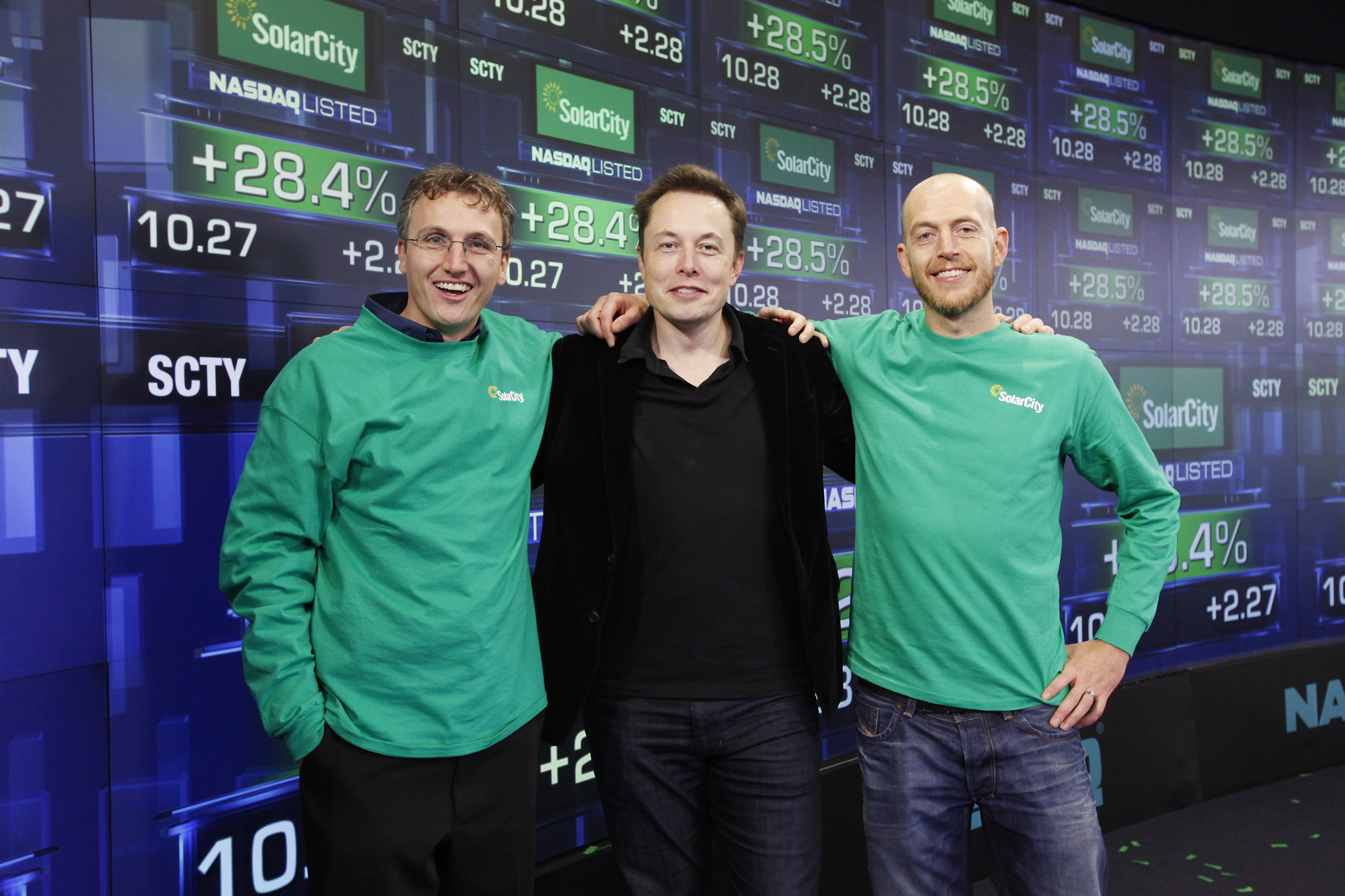 IMAGE DISTRIBUTED FOR SOLARCITY - SolarCity Founder & CEO Lyndon Rive, Chairman Elon Musk, and SolarCity Founder & COO Peter Rive celebrate the companyís IPO by posing for a photo at the NASDAQ Stock Market on Thursday, Dec. 13, 2012 in New York. SolarCity is a leader of distributed clean energy and will trade under SCTY. (Mark Von Holden/AP Images for SolarCity) ORG XMIT: CPA106