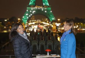 The Mayor of Paris Anne Hidalgo (L) and the French Minister for Ecology, Sustainable Development and Energy Segolene Royal posent in front of the illuminated Eiffel Tower (Tour Eiffel) in Paris on November 4, 2016, to celebrate the first day of the application of the Paris COP21 climate accord. The worldwide pact to battle global warming entered into force on November 4, just a week before nations reassemble to discuss how to make good on their promises to cut planet-warming greenhouse gases. Dubbed the Paris Agreement, it is the first-ever deal binding all the world's nations, rich and poor, to a commitment to cap global warming caused mainly by the burning of coal, oil and gas.  / AFP / PATRICK KOVARIK        (Photo credit should read PATRICK KOVARIK/AFP/Getty Images)